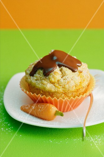 A carrot muffin topped with chocolate glaze next to a marzipan carrot