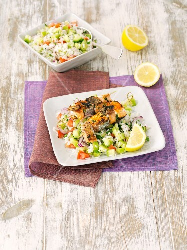 Salmon skewers with rice and a tomato and cucumber salad