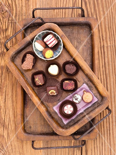 Various chocolate pralines on a wooden tray