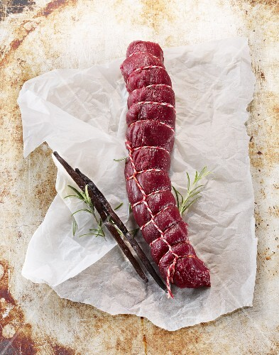 Raw saddle of venison with rosemary and vanilla pods on a piece of paper
