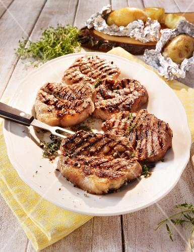 Wild boar steaks with a thyme and juniper berry marinade served with baked potatoes