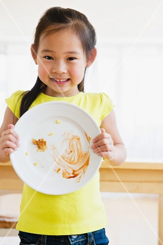 A little girl holding a cleared plate