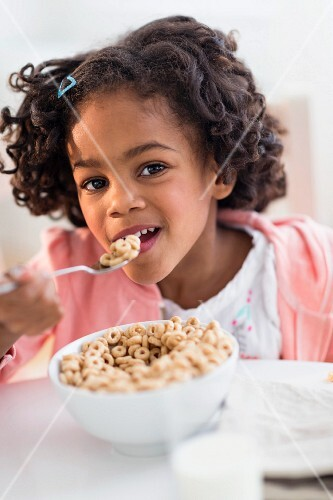 A little girl eating cereal for breakfast