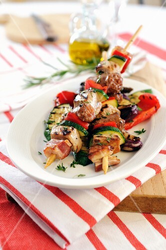 Barbecued kebabs with sausage, bacon and pancetta on grilled vegetables