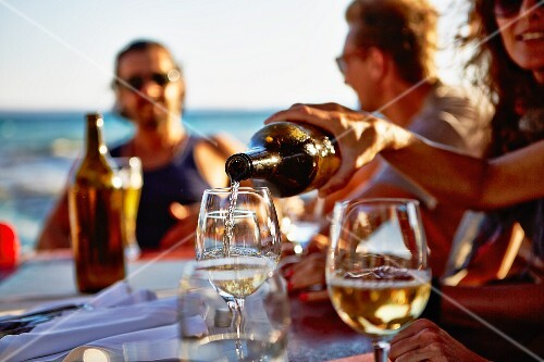 Young people drinking wine at a table in a restaurant overlooking the sea