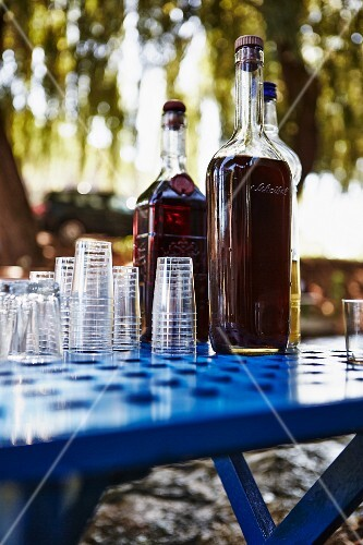 Bottles of mastika (shnapps, Croatia) with glasses on a table in a garden