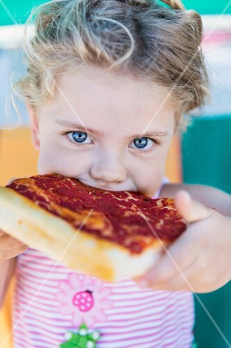 A little girl taking a big bite from a slice of pizza