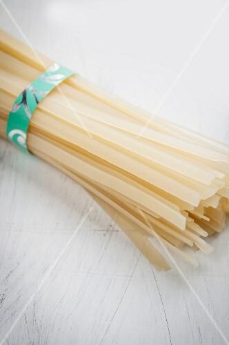 A bundle of flat, Asian rice noodles