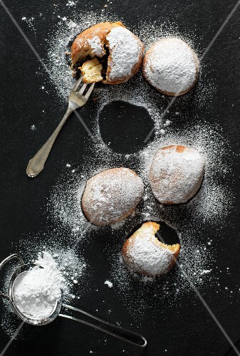 Doughnuts with icing sugar on a black surface