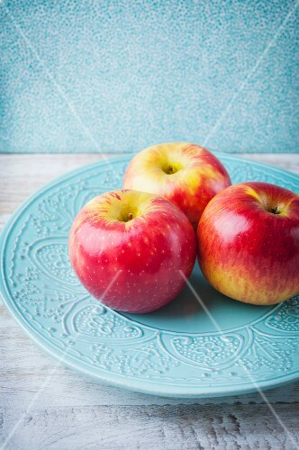 Three Pink Lady apples on a blue ceramic plate