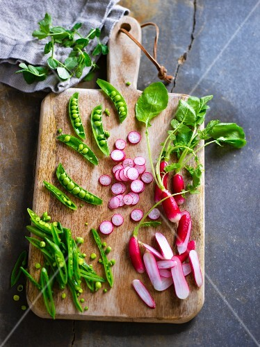 Ingredients for spring salad with peas and radishes on a chopping board
