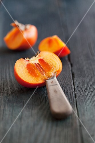 A persimmon, sliced, on a wooden surface