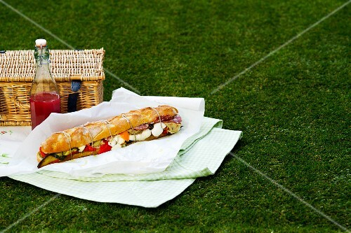 A baguette sandwich, a bottle of champagne and a picnic basket