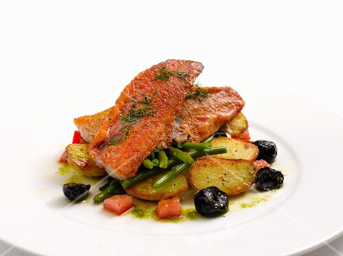 Red mullet fillet on a bed of potatoes with green beans and olives