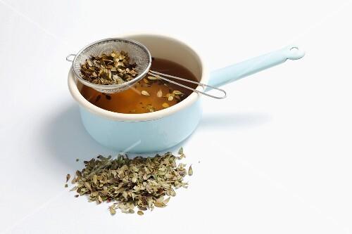 A saucepan of manzanita tea with dried tea leaves next to it