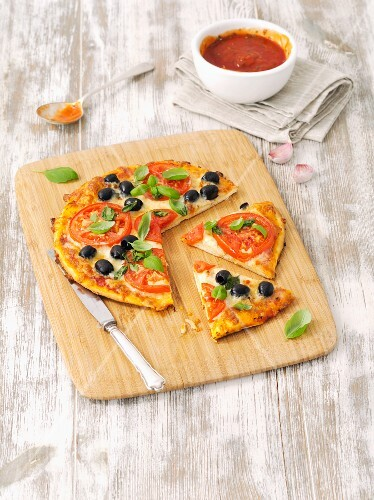 Homemade pizza with tomatoes, black olives and basil