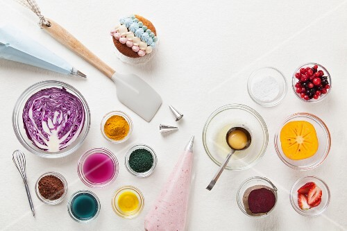 A decorated cupcake, food colouring, fruits and a piping bag