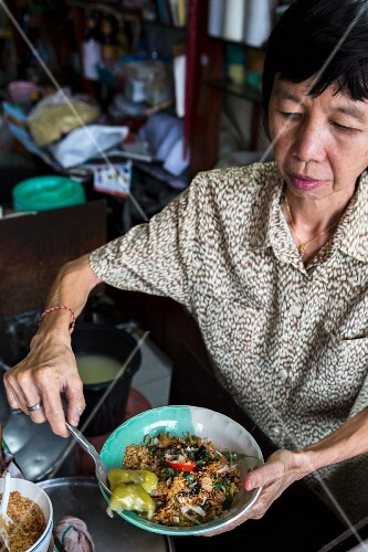 A woman serving a noodle dish made with Hokkien noodles, Thailand