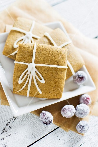 Square gingerbread biscuits made with molasses and ginger, decorated with iced bows