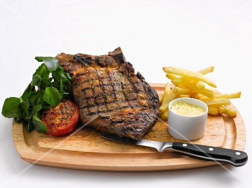 Grilled beef steak with chips, herb butter and tomatoes