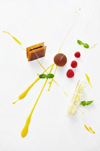 A dessert platter with chocolate truffles, raspberries and mango sauce