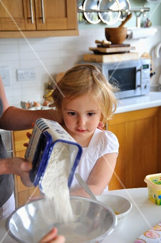 A little girl helping her mother with baking