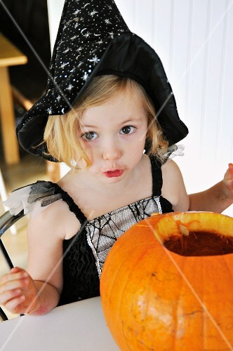 A little girl in a Halloween costume with a pumpkin