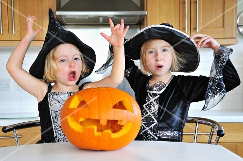 Two girls in the kitchen with a Halloween pumpkin