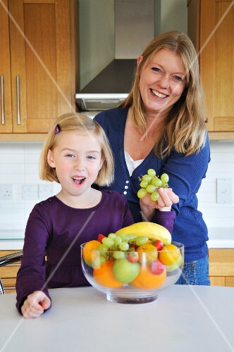 A mother and daughter in the kitchen with a bowl of fruit