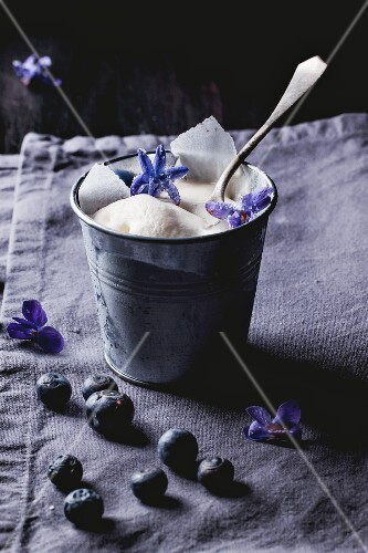Vanilla ice cream with blueberries and sugared violets in a small metal cup