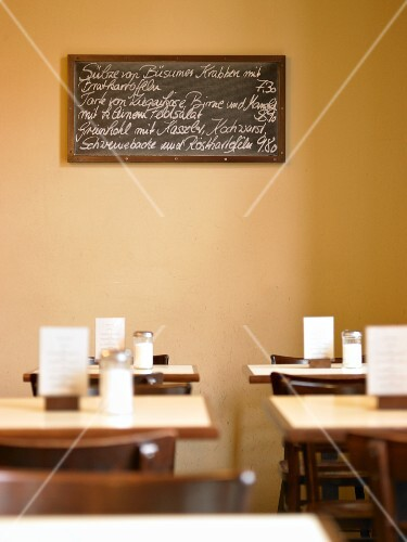 A hand-written menu on a board in the sunny dining room of a restaurant