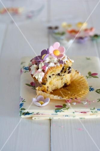 Cupcake mit Zuckerblumen, zur Hälfte angebissen