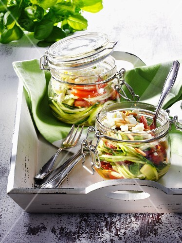 Jars of preserved courgettes with tomatoes and feta cheese