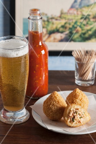Coxinhas (fried chicken croquettes, Brazil) with a spicy sauce and a glass of beer