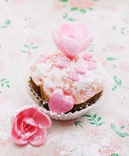 A cupcake decorated with sugar hearts and flowers for Valentine's Day