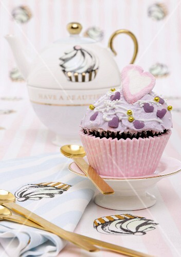 A cupcake decorated with purple buttercream for Valentine's Day