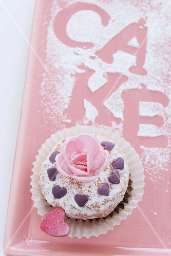 A cupcake decorated with a sugar rose and a hearts for Valentine's Day