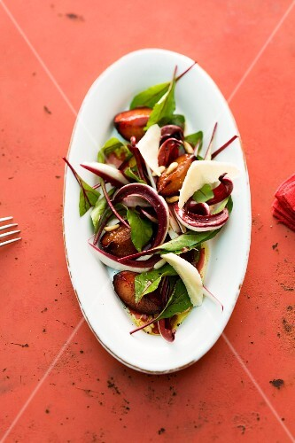 A salad made with glazed plums, radicchio and beetroot leaves