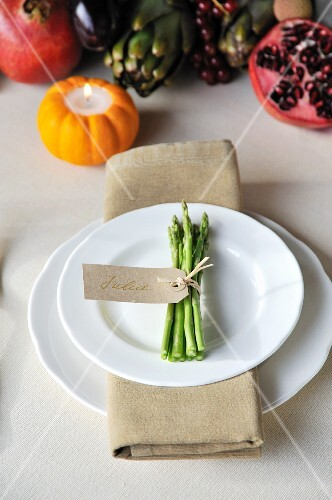 A place setting with a bunch of asparagus tied with a name tag