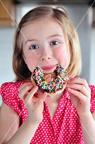 A little girl eating a doughnut with sugar sprinkles