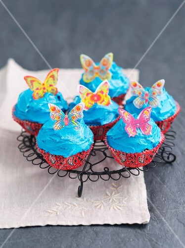 Cupcakes decorated with blue buttercream and butterflies