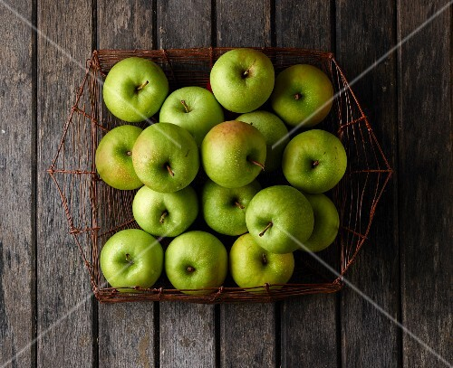 Granny Smith apples in a wire basket (seen from above)