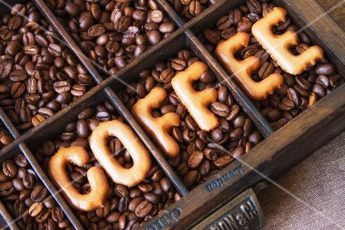 The word 'coffee' written using alphabet biscuits on top of coffee beans
