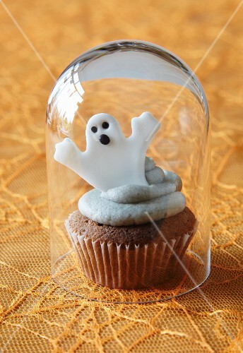 A cupcake decorated with a ghost for Halloween under a glass cloche