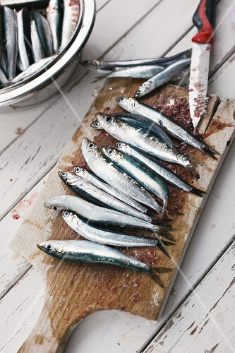 Fresh anchovies being scaled on a chopping board