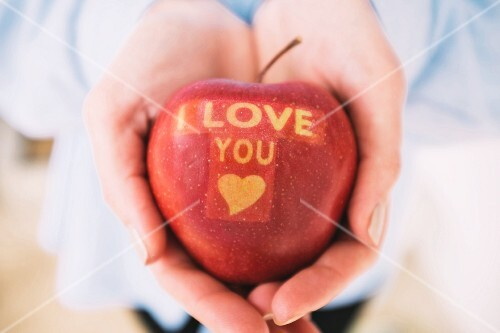 A women holding an apple carved with the words I LOVE YOU and a heart
