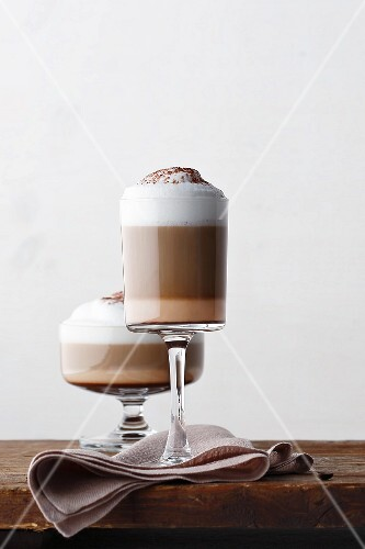 Two glass of winter coffee on a brown napkin on a wooden table