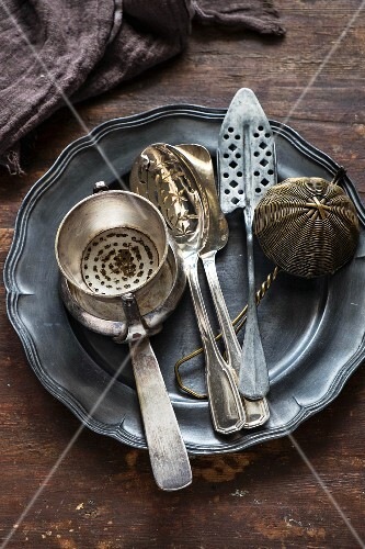 Silver kitchen utensils on a pewter plate and on a wooden surface