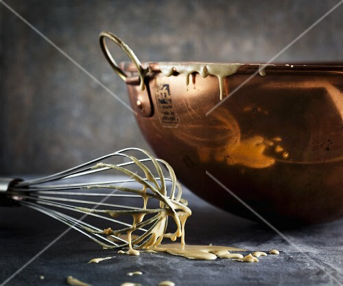 Cake mixture on a whisk next to a mixing bowl