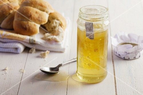 A honeycomb in a jar of honey next to bread rolls on a tea towel
